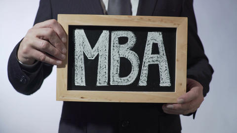 MBA written on blackboard, business person holding sign, business education Footage