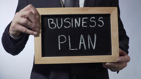 Business plan written on blackboard, male hands holding sign, strategy, goals Footage