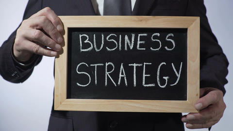 Business strategy written on blackboard, male in black suit holding sign, career Footage