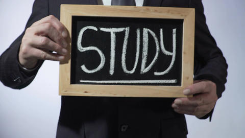 Study written on blackboard, businessman holding sign, career and future Footage