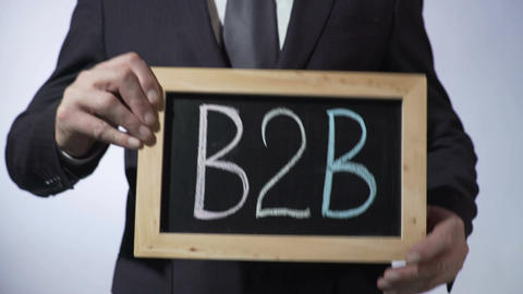 B2B, business-to-business rule written on blackboard, man holding sign, sales Footage