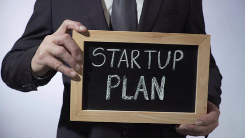 Startup plan written on blackboard, businessman holding sign, business concept 영상물