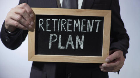 Retirement plan written on blackboard, businessman holding sign, money savings Footage
