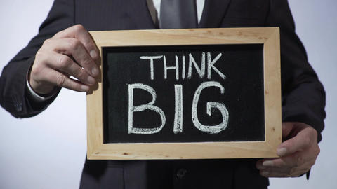 Think big written on blackboard, male in suit holding sign, motivational concept Footage