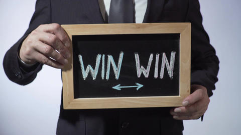 Win-Win written on blackboard, businessman holding sign, business concept Footage