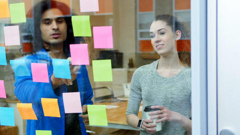 Executives discussing over sticky notes Live Action