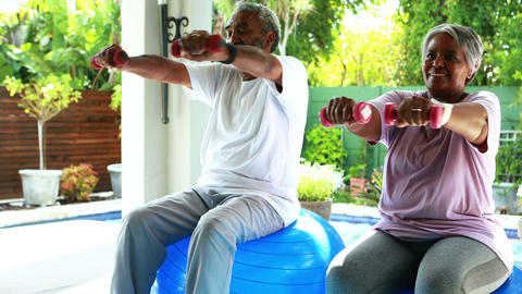 Senior couple exercising with dumbbell at home Live Action
