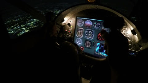 Male pilot hands holding steering wheel, preparing plane for landing at night Footage