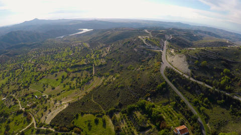 Camera flying above majestic green hills with olive trees, mountains on horizon Footage