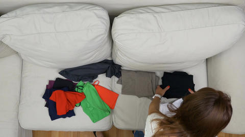 Top view of girl choosing and folding clothes ready for summer holiday Footage