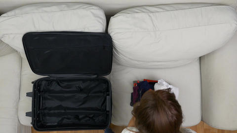 Timelapse of woman packing clothes into a suitcase for travel Footage