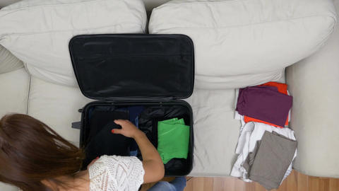 Young woman carefully preparing travel bag for summer trip Footage