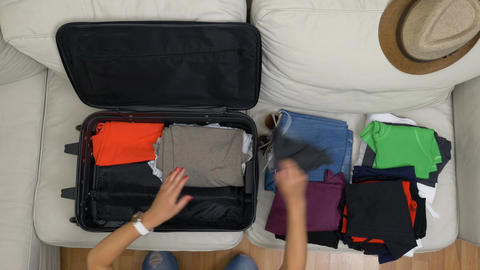 Top view of young woman organizing clothes into suitcase Footage