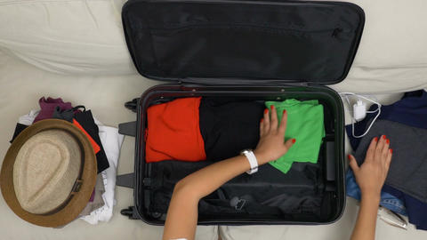Top view of woman hands with red nails filling suitcase with folded clothes for  Footage