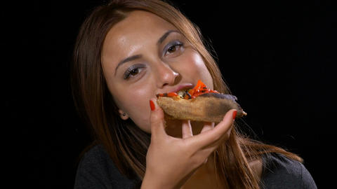 Pretty girl unhealthy eating a slice of pizza and smiling Footage