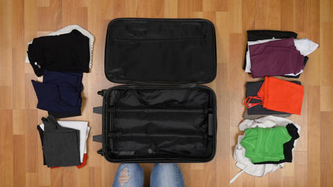 Top view travel concept of woman sorting and packing her clothes into suitcase Footage