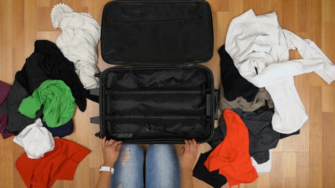 Top view of woman throwing clothes into a suitcase closing and leaving in a hurr Footage