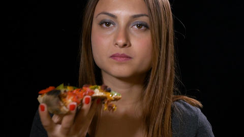 Closeup of happy woman eating and enjoying a slice of pizza and laughing Footage