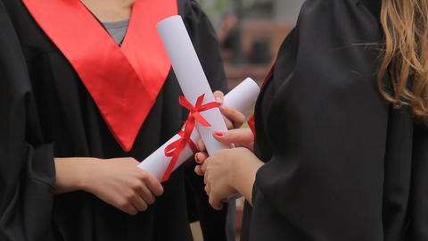 Hands of female graduates holding diplomas tied with red ribbons, conversation Footage