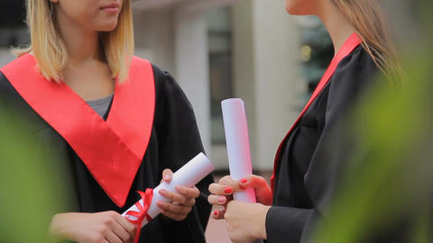 Two pretty students talking in park after graduation ceremony, happy future Footage