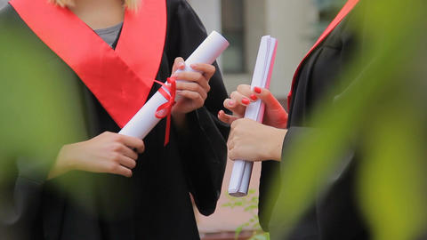 Female students holding diplomas and chatting in park, higher education Footage