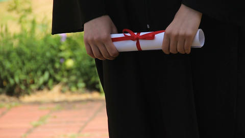 Hands of graduate holding diploma certificate tied with red ribbon, graduation Footage