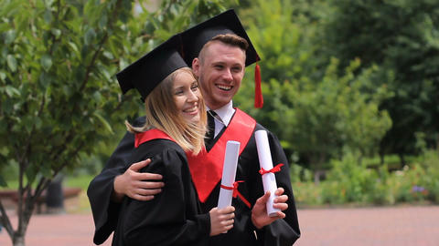 Cheerful couple of graduates holding diplomas and posing for camera, students Footage