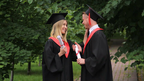 Excited smiling graduates holding diplomas and talking about future in park Footage