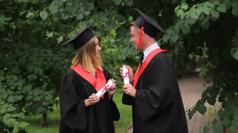 Happy male and female graduates chatting about future in park, graduation day Footage