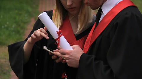 Serious male and female students in academic dresses reading news on smartphone Footage