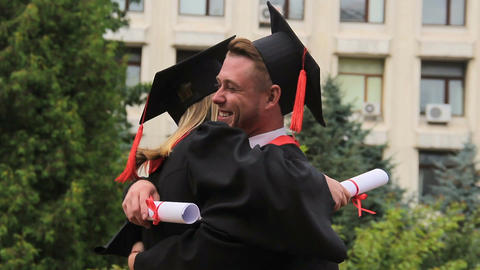 Best friends in academic dresses and hats hugging and smiling on graduation day Footage
