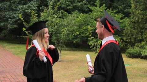 Happy graduates holding diplomas and embracing in park near academy, joy Footage