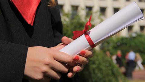 Close-up of female hands holding diploma with red ribbon, graduation ceremony Footage