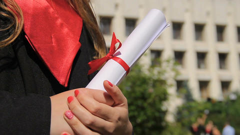 Woman dressed in graduation gown holding diploma, looking into happy future Footage