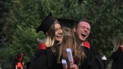 Excited group of graduating students congratulating each other after ceremony Footage