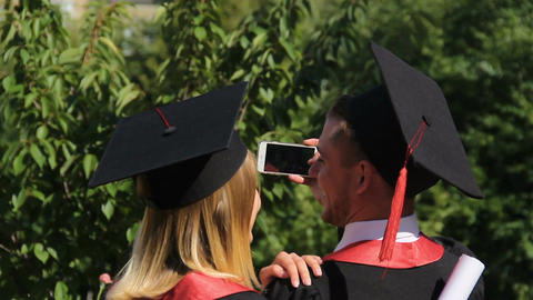 Couple of joyful graduates recording video on smartphone, graduation ceremony Footage