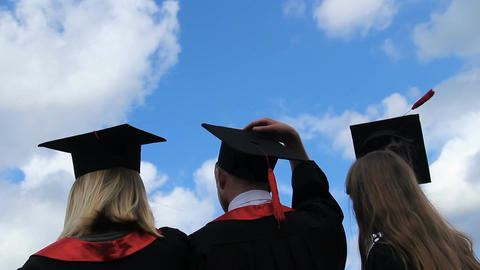 Happy future of graduates, three students throwing academic caps up in the air Footage