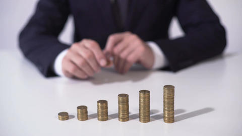 Banker putting coin on pile, deposit interest growing, successful investment Footage