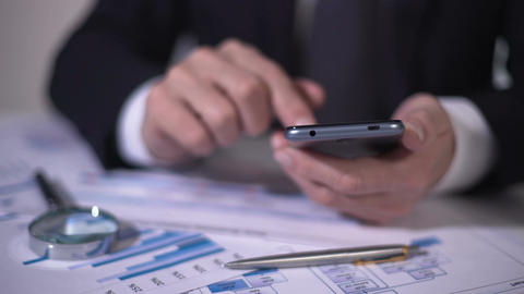 Investor scrolling market newswire on smartphone, examining data for new project Footage