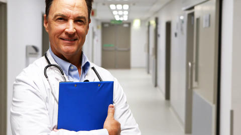 Portrait of doctor holding clipboard in corridor Footage