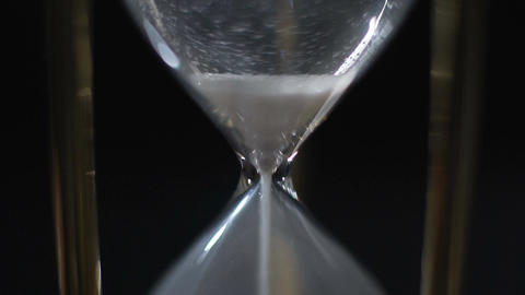 Last grains of sand falling in hourglass, time running out, end of life, closeup Footage
