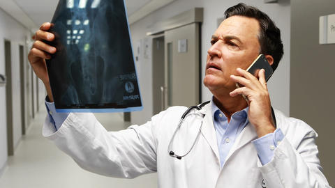 Male doctor talking on mobile phone while talking on mobile phone in corridor Footage