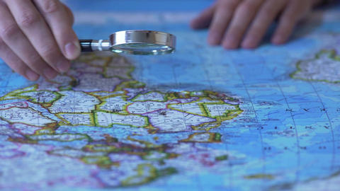 Person looking at Africa on map through magnifying glass, trip destination Live Action