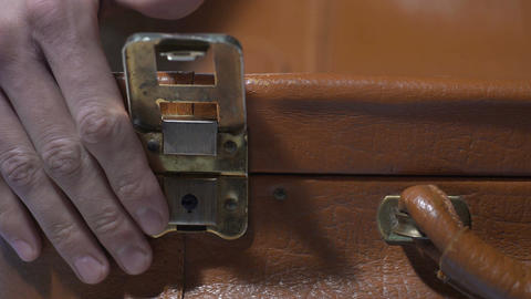 Man shutting vintage leather suitcase, packing for vacation, preparing for trip Footage