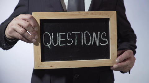 Questions written on blackboard, business person holding sign, FAQ, advice Footage