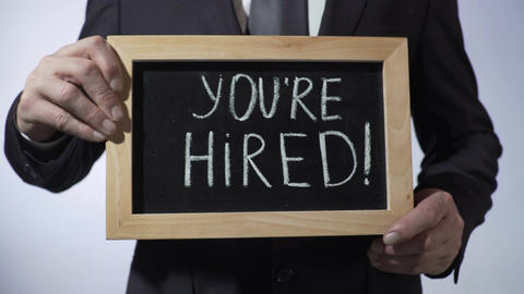 You're hired written on blackboard, businessman holding sign, business concept Live Action