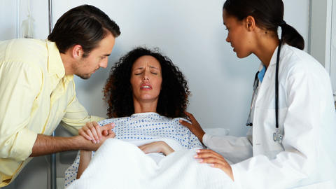 Doctor and man comforting pregnant woman in ward Footage