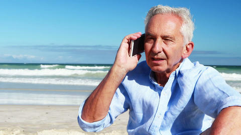 Senior man talking on mobile phone on the phone at the beach Live Action