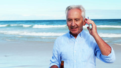 Senior man talking on mobile phone on the phone at the beach Live-Action