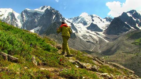 Man traveler walks against high mountains Footage
